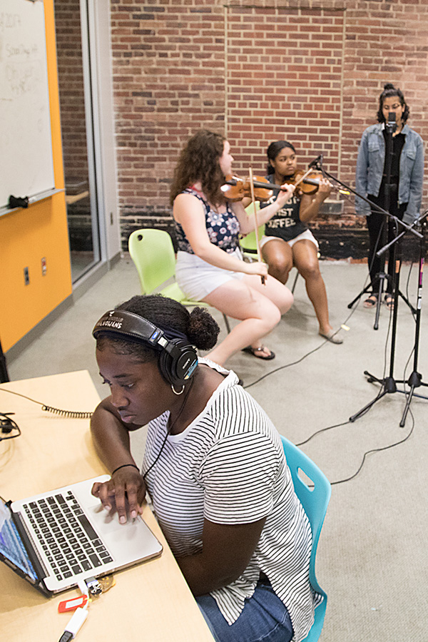 Photograph of a Baltimore School for the Arts recording other students playing violins and singing