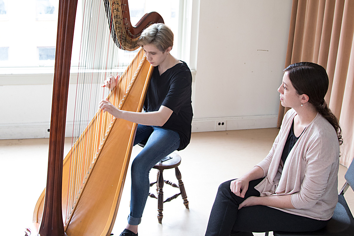 Photo of teacher, and student playing harp